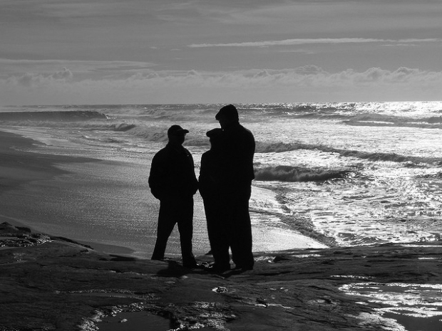Silhouettes of three men talking on a twilit beach in Portugal.